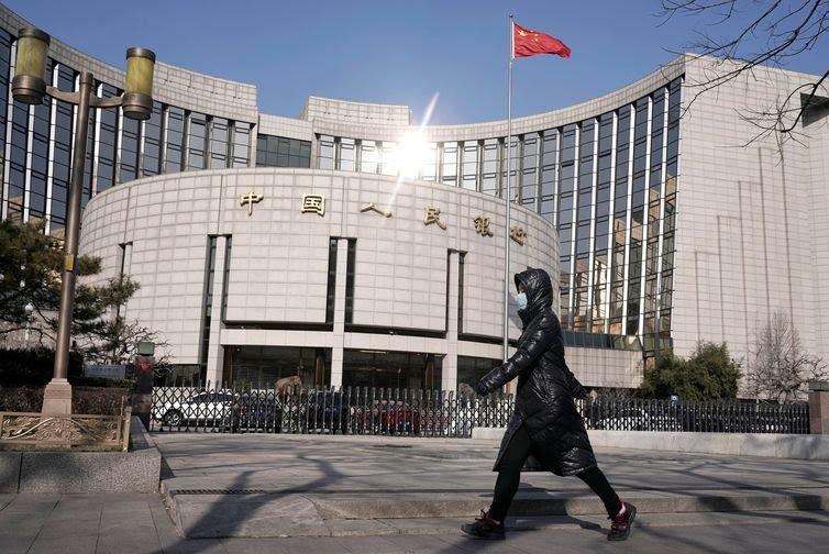 Uma mulher usando uma máscara passa pela sede do Banco Popular da China, o banco central, em Pequim, na China, quando o país é atingido por um surto do novo coronavírus, em 3 de fevereiro de 2020. REUTERS / Jason Lee